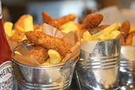 Freshly cooked chunky Fish bites and Chips from Fruits & Fountains in stainless steel serving pails